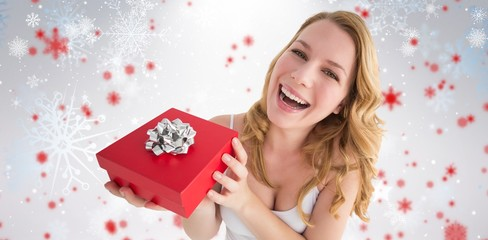 Composite image of portrait of a happy woman receiving a present