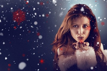 Composite image of festive redhead blowing a kiss