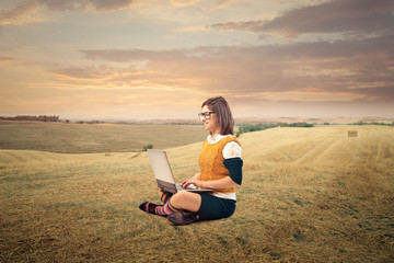 Woman sitting in the countryside using a laptop