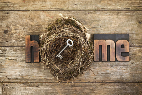 Home, word written with letterpress printing blocks and bird nest with key on rustic wood