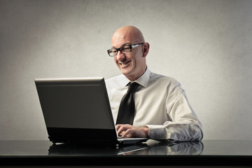 Smiling businessman using a pc