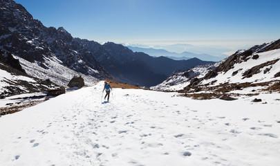 Wall Mural - Woman backpacker tourist walking snow mountain back view.