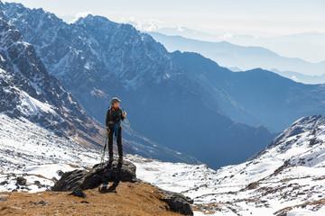 Wall Mural - Young woman tourist backpacker standing rock mountain edge.