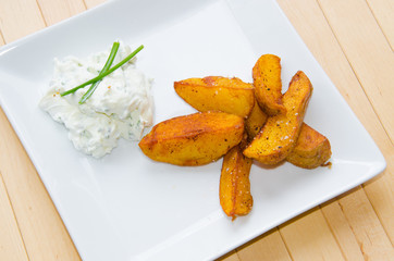 Upper view on a plate with fried potatoes and creamy dip on wooden background