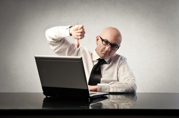 Disappointed businessman sitting in front of a laptop