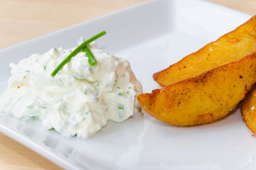 Creamy dip with herbs and fried potatoes on white plate lying on wooden background