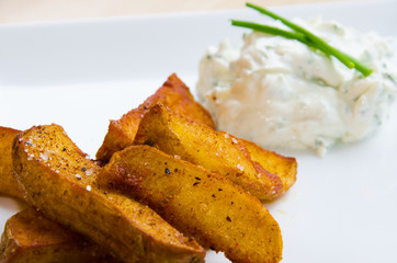 Fried potatoes on white plate with creamy dip