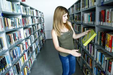 Giovane e bella studentessa sceglie un libro in biblioteca