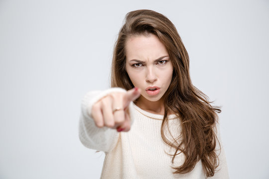 Angry woman pointing finger at camera