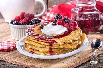 Pancakes with cream, raspberries and blackberries on the table