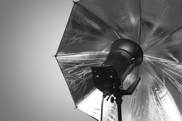 photography studio strobe flash with silver umbrella and gray co