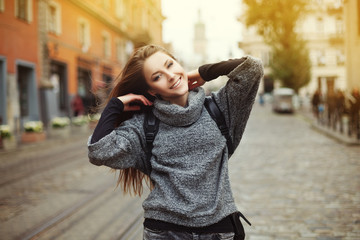 Happy young smiling woman playing with her long beautiful hair. Toned
