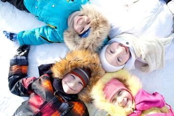 Joyful children lie on their backs on a winter outing