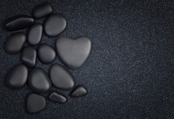 Black stones with black zen heart shaped rock on grain sand