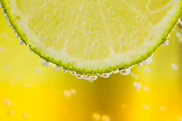 Green lime with water splash. Yellow background.
