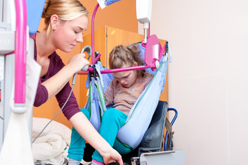Disability/ A disabled child is lifted into a wheelchair by a nurse using special needs lifting equipment