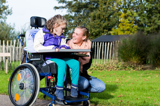 Disability/ A disabled child in a wheelchair with a carer going for a walk