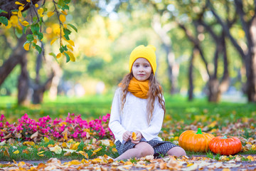 Wall Mural - Adorable little girl with pumpkin at beautiful autumn park. Trick or treat