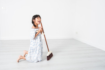 Happy Asian girl with a cleaning in white room.
