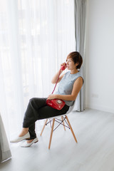 Smart Asian woman sitting and holding red vintage phone near win