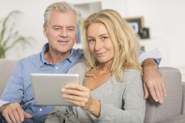 Mature couple sitting in sofa and using tablet pc