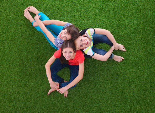 Young women sitting  on green grass