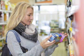 Mature woman in a supermarket choosing tea