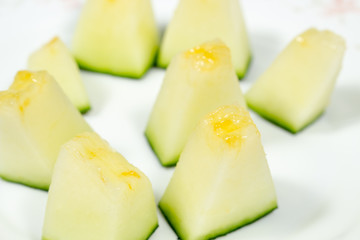 Melon chunks of the Santa Claus variety on a white dish