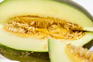 "Close-up of sliced Santa Claus melon, also known as ""toad skin"" due its green-striped rind"