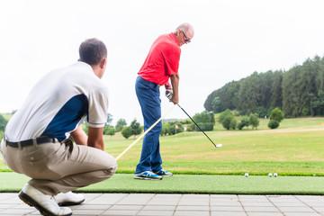 Golflehrer trainiert Golfer auf Driving Range