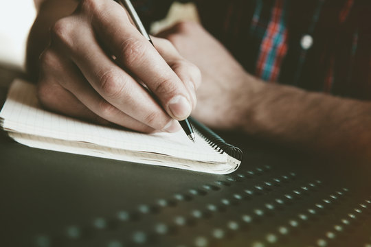 male hand writing in notebook with pen