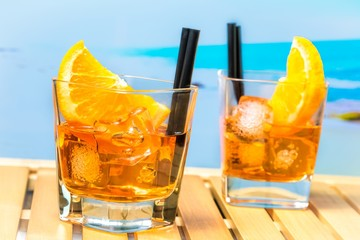 Fototapete - two glasses of spritz aperitif aperol cocktail with orange slices and ice cubes on blur beach background