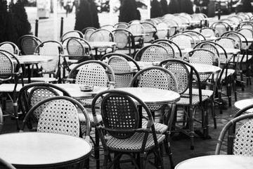 vintage street cafe in Paris, black and white photo of wicker chairs and tables