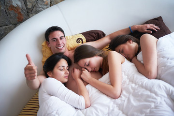handsome man in bed with three beautiful woman