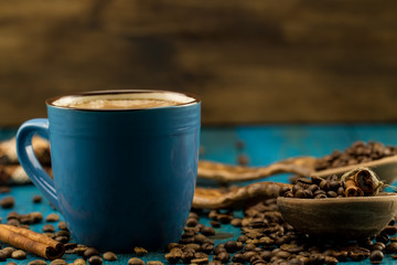 coffee Cup and beans on a blue wooden background