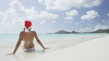 Wall Mural - Christmas beach vacation travel woman wearing Santa hat and bikini enjoying winter holidays getaway on tropical beach. Multicultural Asian Chinese / Caucasian model happy sitting in sand. RED EPIC.