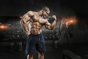 Athlete muscular bodybuilder man demonstrates his muscles in the gym Wall mural
