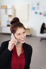 lächelnde frau telefoniert im büro mit ihrem handy