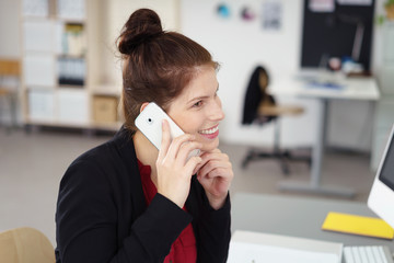 lachende frau telefoniert mit ihrem smartphone im büro