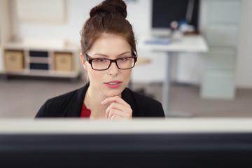 geschäftsfrau im büro schaut konzentriert auf ihren bildschirm