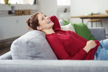 lachende frau lehnt sich auf dem sofa zurück
