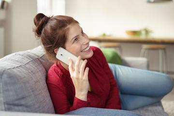 glückliche frau telefoniert mit ihrem smartphone zu hause