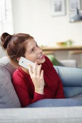 frau liegt entspannt auf dem sofa und telefoniert