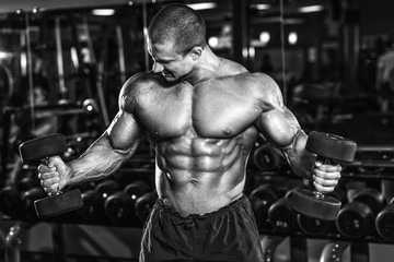 Athlete muscular bodybuilder in the gym training biceps with dumbbells Wall mural