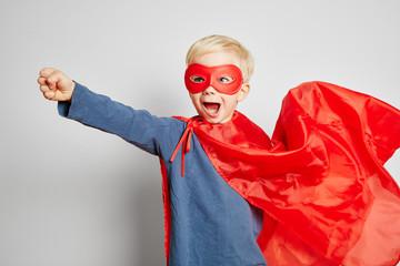 Kind als Superheld mit Faust und Cape