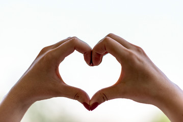 Two female hands shaping a heart, close up