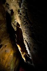 spotlight on flowstone/ limestone in dark cave, close up