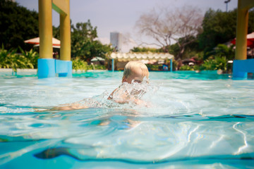 small blonde girl bathes laughs in transparent water of pool