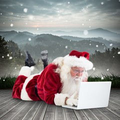 Composite image of santa lies in front of his laptop