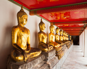 Row of golden and dark buddhas statue in front of wite wall in a
